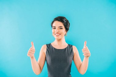 Cheerful mixed race woman showing thumbs up and smiling at camera isolated on blue stock vector