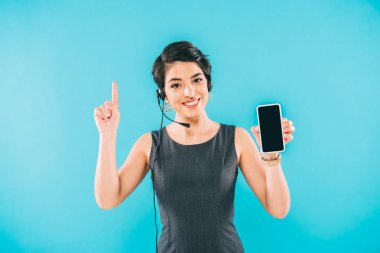 attractive mixed race call center operator showing idea sign and holding smartphone with blank screen isolated on blue