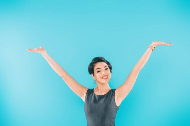 Excited mixed race woman posing at camera with raised hands isolated on blue stock vector