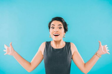 Excited mixed race woman gesturing while looking at camera isolated on blue stock vector