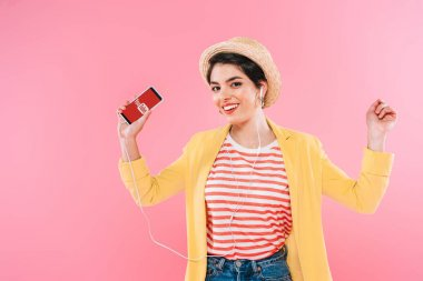 KYIV, UKRAINE - APRIL 24, 2019: Cheerful mixed race woman holding smartphone with Youtube app on screen and listening music in earphone isolated on pink.
