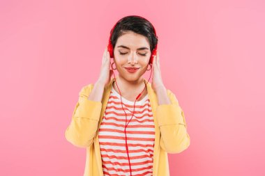 dreamy mixed race woman listening music in headphones with closed eyes isolated on pink