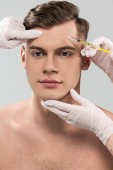 cropped view of cosmetologists in latex gloves doing beauty injection isolated on grey