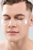 portrét hezkého mladého muže s oční skvrnami izolované na šedé