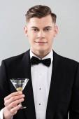 pohled na usmívající se mladého muže ve formálním oblečení s motýlem přidržením sklenice koktejlového skla izolovaného na šedé