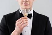oříznutý pohled na usmívajícího se muže ve formálním opotřebení přidržením sklenice koktejlového skla izolovaného na šedé
