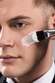 zblízka pohled na člověka, který používá krém na obličeji s kosmetickým kartáčkem