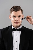 cropped view of cosmetologist applying cream and man in formal wear isolated on grey