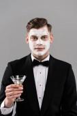 pohled na člověka ve formálním opotřebení se smetanou na obličeji sklenice koktejlového skla izolovaná na šedé