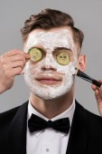 partial view of cosmetologists applying cucumber mask and man in formal wear isolated on grey