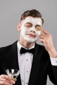 young man in formal wear with face mask holding glass of cocktail and applying cut cucumber on eye isolated on grey