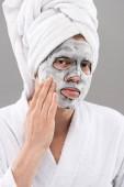 Fotografie Mann im Baderom berühren Gesichtsmaske und Blick auf Kamera isoliert auf grau