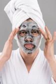 Vorderansicht des Mannes im Bademantel mit Gesichtsmaske isoliert auf grau