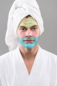 front view of man in bathrobe with facial mask isolated on grey
