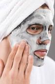 Porträt des Mannes mit Handtuch auf dem Kopf mit schaumigen Gesichtsmaske blickweg