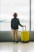 pohled na chlapce stojící u okna, držící žlutý kufr