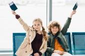 bambini felici seduti su sedili blu, in possesso di passaporti e biglietti in sala dattesa in aeroporto