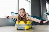 eccitato bambino preteen sdraiato sulla valigia con le mani tese nella sala partenze aeroportuali