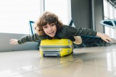 excited preteen kid lying on suitcase with outstretched hands in airport departure lounge