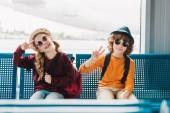 předškolní děti v brýlích sedícího v čekárně a zobrazující mírové znaky