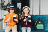 Fotografie niedliche preteen Kinder sitzen in Wartehalle mit Wasserflaschen, Pässe und Flugtickets
