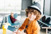 cute preteen boy with passport and air ticket in airport