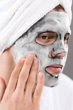 portrait of man with towel on head with foamy facial mask looking away