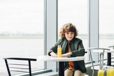 Boy sitting at table with orange juice on it and waiting hall in airport stock vector