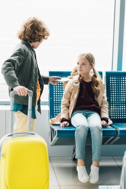 full length view of boy holding yellow suitcase and giving passport to preteen kid sitting on blue seat in waiting hall in airport