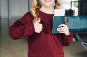 cropped view of preteen kid with passport and air ticket showing thumb up in airport