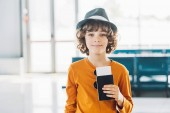 předškolní chlapec s pasem a letenkou na letišti, pohled na kameru