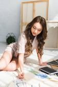 Fotografie attraktive lockige Designer sitzen auf Teppich und Zeichnung in der Nähe von Notebooks