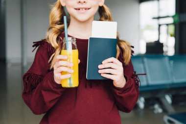 Cropped view of preteen kid with air ticket, passport and orange juice in airport stock vector