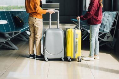 Back view of preteen kids with suitcases in waiting hall