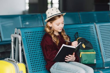 preteen kid sitting in waiting hall and writing in notebook