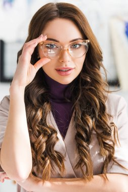 Attractive young woman touching glasses and looking at camera stock vector