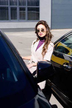 Selective focus of serious young woman in sunglasses standing near cars stock vector