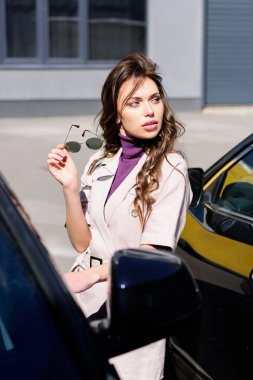 selective focus of serious young woman holding sunglasses near cars