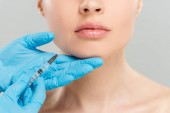 cropped view of cosmetologist holding syringe near face of woman isolated on grey