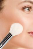 oříznutý pohled žena aplikování modše na tvář kosmetickým kartáčkem