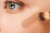 cropped view of cosmetic brush with brown blush on cheek of woman