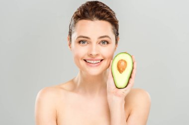 Cheerful naked woman holding half of organic and ripe avocado isolated on grey stock vector