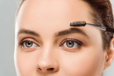 Cropped view of woman shaping eyebrow with eyebrow brush isolated on grey stock vector