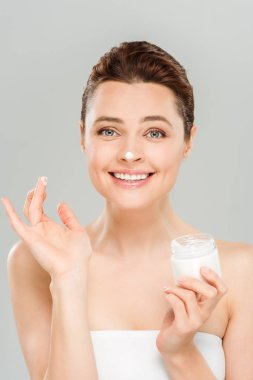 cheerful woman applying face cream and smiling isolated on grey