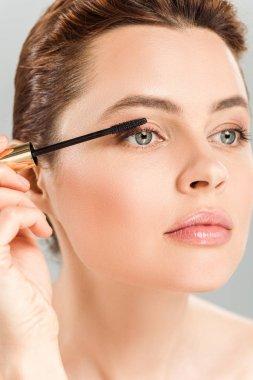 attractive woman applying mascara isolated on grey