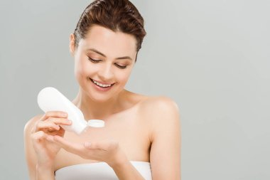 cheerful woman applying body lotion while holding bottle isolated on grey