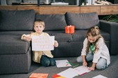 cute boy showing drawing while sitting on floor near sofa together with sister