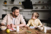 Fotografie father and son drawing while sitting at kitchen table with served breakfast