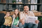 happy family showing thumbs up while father holding travel life newspaper