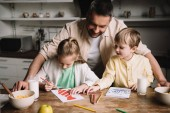 Fotografie happy daddy standing near adorable kids drawing fathers day greeting cards while sitting at kitchen table with served breakfast